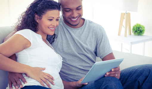 Pregnant Couple With Laptop Computer