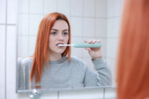 Red haired woman brushig her teeth